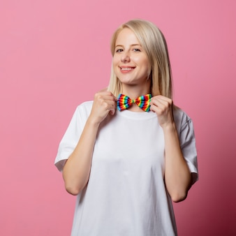 Blonde woman in white tshirt with bow tie lgbt on pink