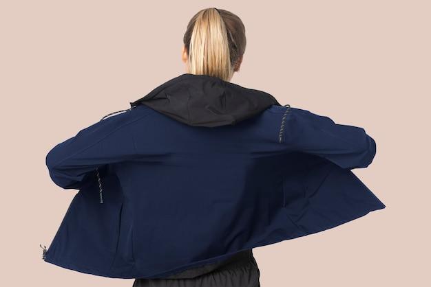 Donna bionda in giacca a vento per servizio fotografico di moda sportiva vista posteriore