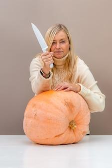 Блондинка с ножом с тыквой