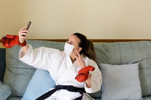 自宅で空手を練習するマスクを持つブロンドの女性。トレーニング後、ソファで休む