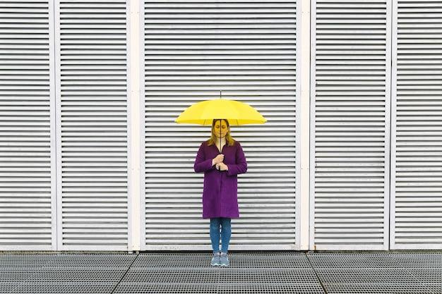 幾何学的な構造の白い壁の前でポーズをとる紫色のコートと黄色の傘を持つブロンドの女性。