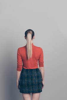 灰色の壁にポーズをとって赤いタートルネックのセーターと金髪の女性