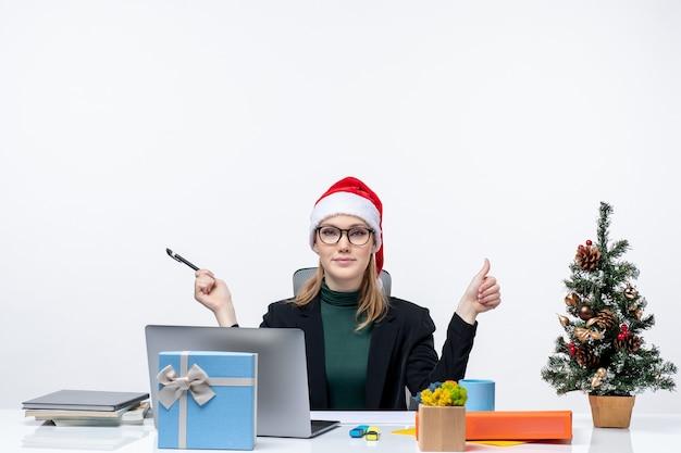 크리스마스 트리와 선물 테이블에 앉아 산타 클로스 모자와 금발 여자
