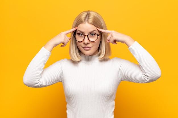 Блондинка с серьезным и сосредоточенным взглядом, мозговой штурм и размышления над сложной проблемой