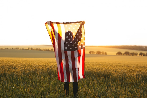 Blonde woman  with the american flag running in a wheat field at sunset.  independence day, patriotic holiday.4th of july.