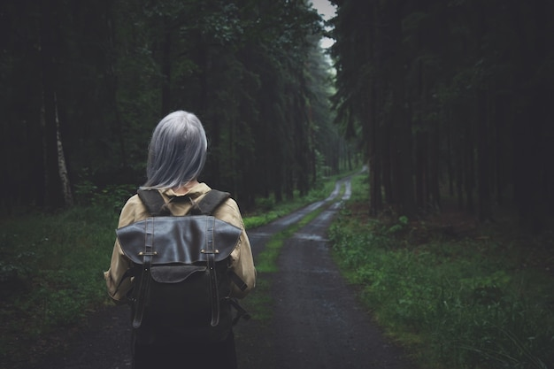Blonde woman with backpack in rainy day in forest