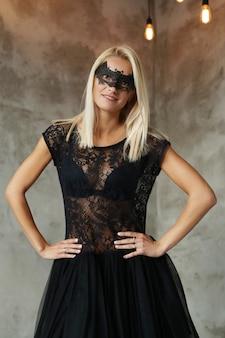 ハロウィーンや仮装パーティー、黒い衣装のコウモリの形のマスクを持つ金髪の女性