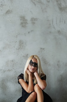 Blonde woman with bat-shaped mask for halloween or masquerade party, and black costume
