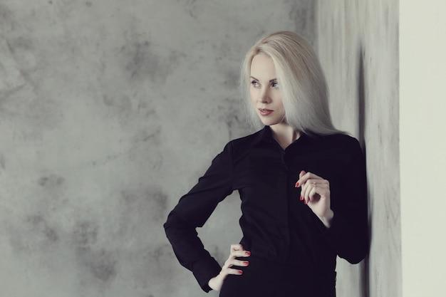 黒のドレスのポーズで金髪の女性