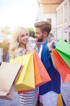 ショッピングバッグを持っているボーイフレンドと金髪の女性