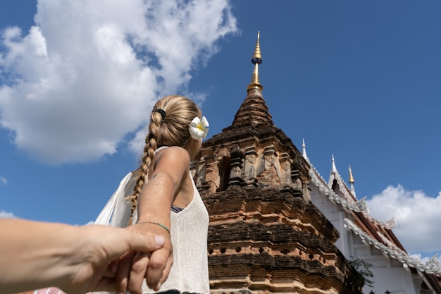 Blonde woman with a braid and a flower in her ear holding hands in front of a buddhist temple
