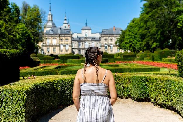 Блондинка с косами смотрит в сторону дворца ла-гранха-де-сан-идельфонсо.