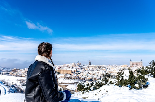 Blonde woman with braids observing the snow-covered city of toledo from a lookout point.