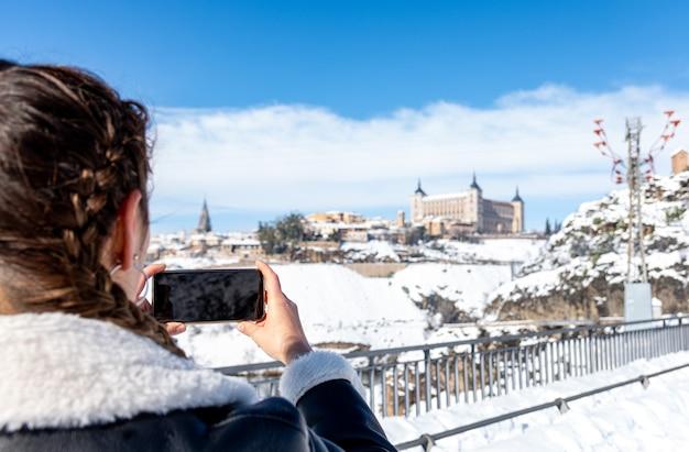 Блондинка с косами фотографирует в городе толедо со своим мобильным телефоном. снежный пейзаж фон.