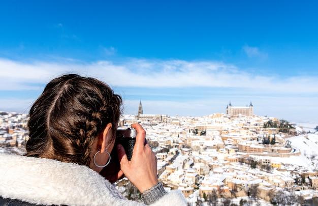 눈 덮인 도시 톨레도의 카메라로 사진을 찍는 머리 띠와 금발 여자.
