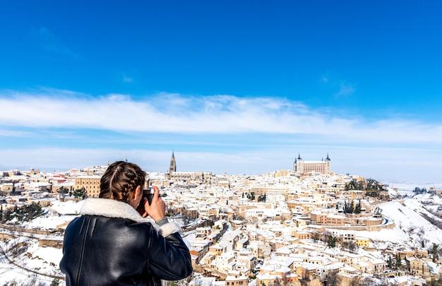 Блондинка с косами фотографирует заснеженный город толедо на камеру.