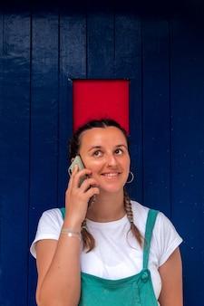 그녀의 휴대 전화에 대 한 얘기 머리 띠와 금발 여자. 빨간색과 파란색 문 배경입니다.