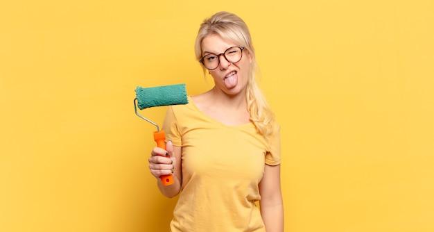 陽気な、のんきな、反抗的な態度、冗談を言ったり、舌を突き出したり、楽しんでいるブロンドの女性
