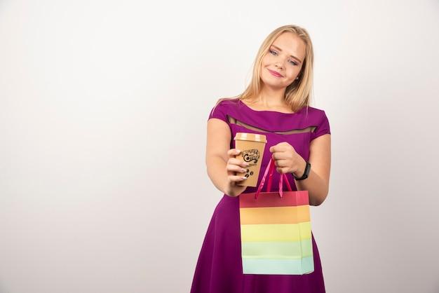 Donna bionda con una tazza di caffè e una borsa in posa.