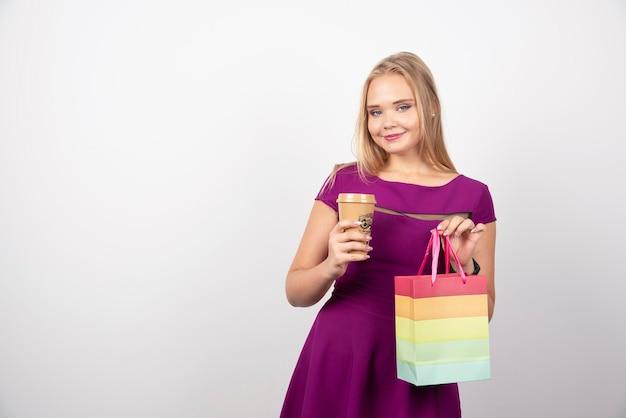 Белокурая женщина с чашкой кофе и представлять мешка. фото высокого качества