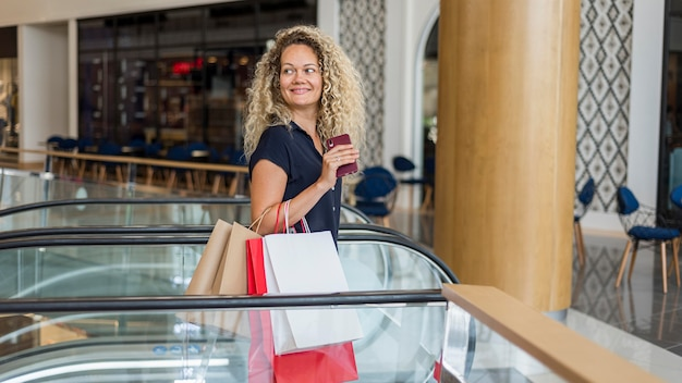 Blonde woman with curly hair carrying shopping bags