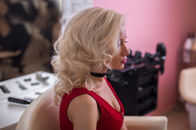 Blonde woman with curly hair in hairdressing salon