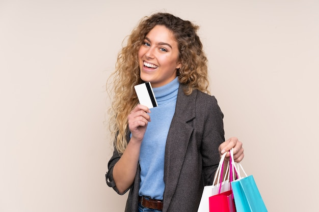 Blonde woman with curly hair isolated on beige background holding shopping bags and a credit card