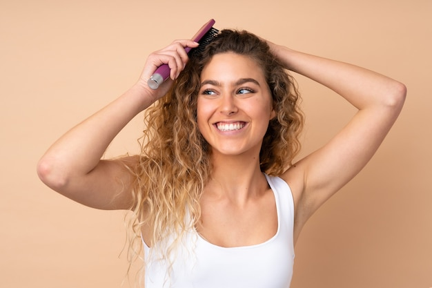 Blonde woman with curly hair isolated with hair comb