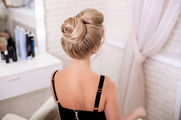 Blonde woman with fashion hairstyle in hairdressing salon