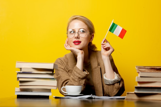 Blonde woman with flag of italy and books on yellow
