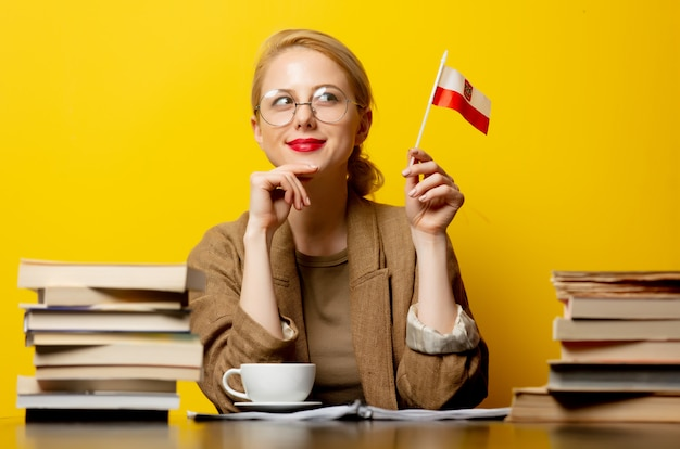 Blonde woman with flag of poland and books on yellow