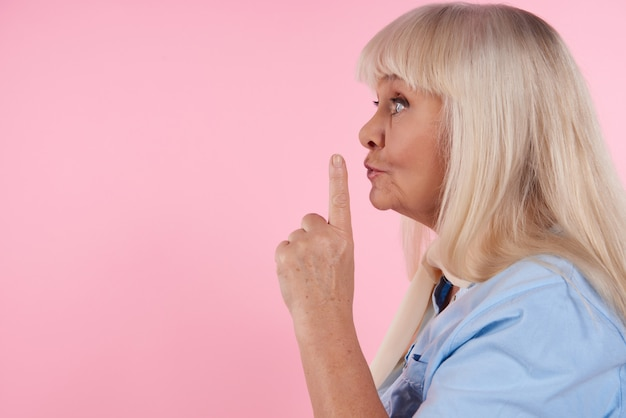 Blonde woman with forefinger at lips shows sign quieter.