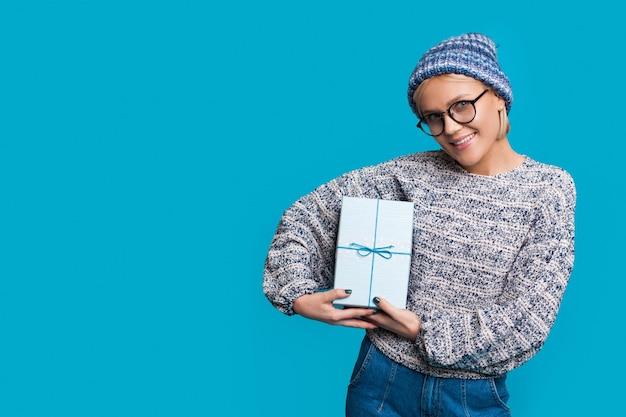 Блондинка в очках и шляпе держит подарок и улыбается в камеру, продвигая что-то на синей стене студии