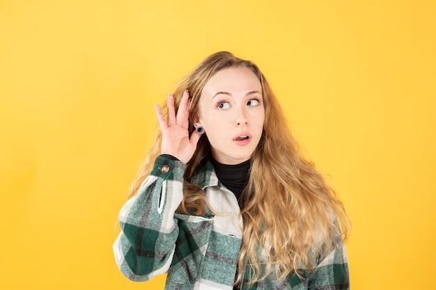 耳に手、聴覚障害黄色の背景を持つブロンドの女性