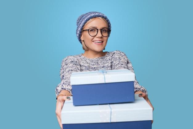 모자와 안경 금발의 여자는 앞에 파란색 벽에 웃 고 휴가에 선물을 받고있다