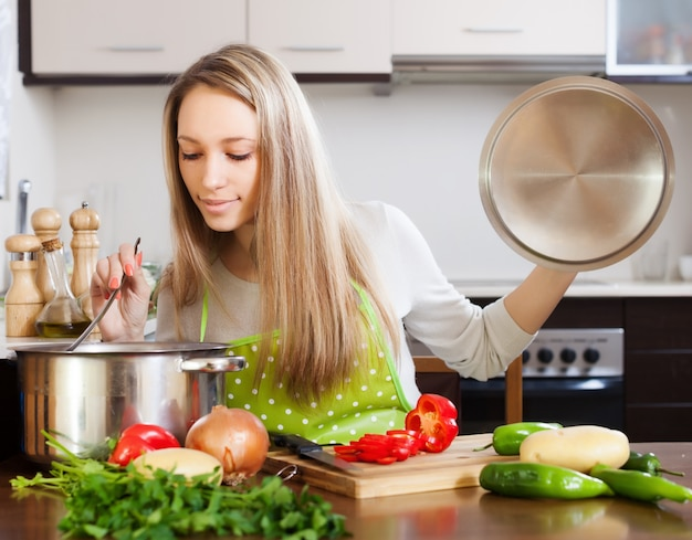 Blonde woman with ladle testing soup from pan