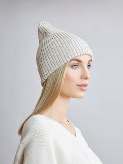 모자와 흰색 스웨터를 입고 긴 머리를 가진 금발의 여자. 여자의 아름다움 초상화, 천연 화장품