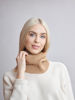 Blonde woman with long hair in a white sweater. beauty portrait of a girl, natural cosmetics