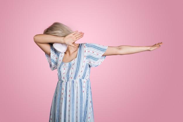 夏のドレスを着てピンクの壁を軽くたたく顔に医療マスクを持つブロンドの女性