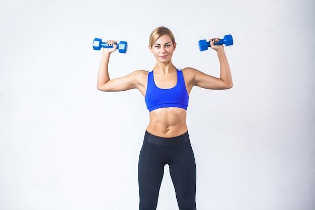 Блондинка с идеальным телом держит две синие гантели