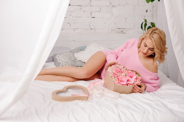 Blonde woman with pink shirt lying on the bed holding the heart shape box of rose colored peonies, orchids and roses