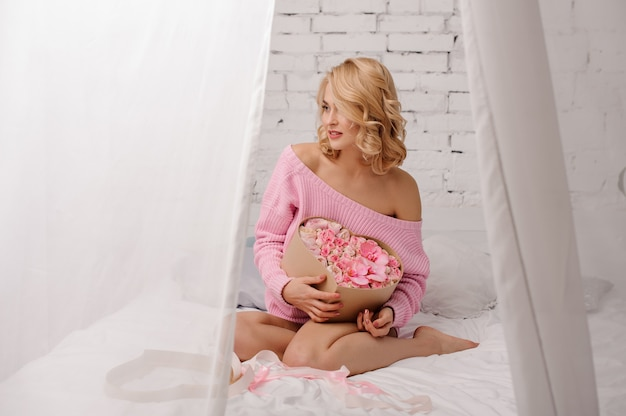 Blonde woman with pink shirt sitting on the bed holding the heart shape box of flowers