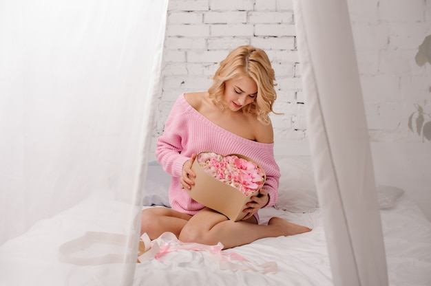 Blonde woman with pink shirt sitting on the bed looking at the heart shape box of flowers