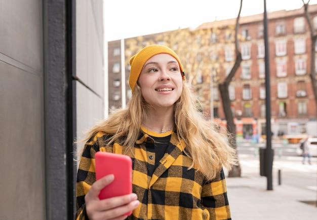 通りの黄色の格子縞のシャツと携帯電話を持つブロンドの女性