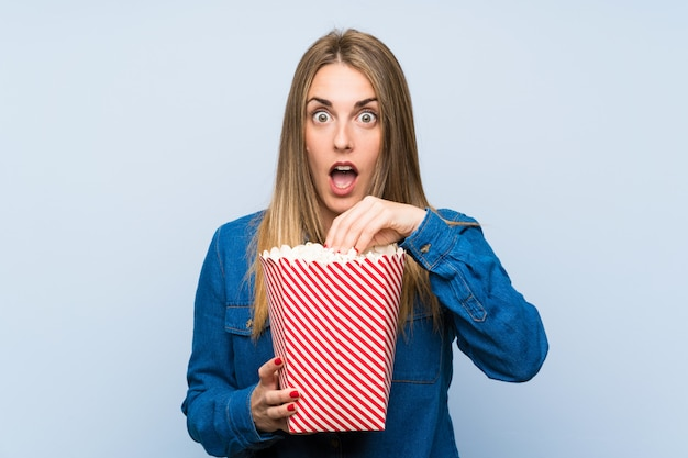 Blonde woman with popcorns over blue wall doing surprise gesture