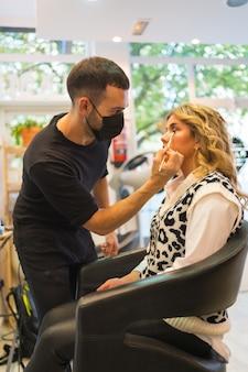 写真撮影の前に化粧をしているブロンドの女性