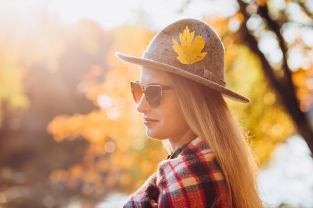 Блондинка с красным клетчатым шарфом стоит в осеннем лесу