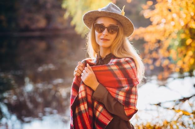 Блондинка с красным клетчатым шарфом стоит у озера