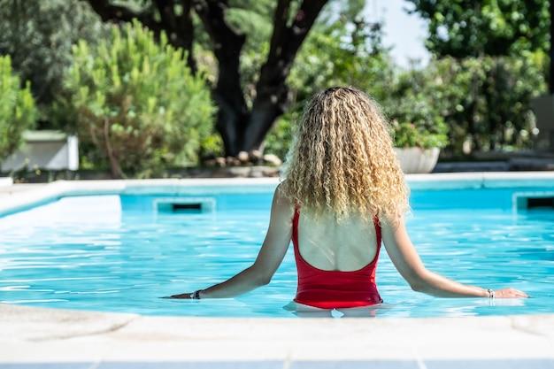 Белокурая женщина с красным купальником на спине в бассейне. летняя концепция