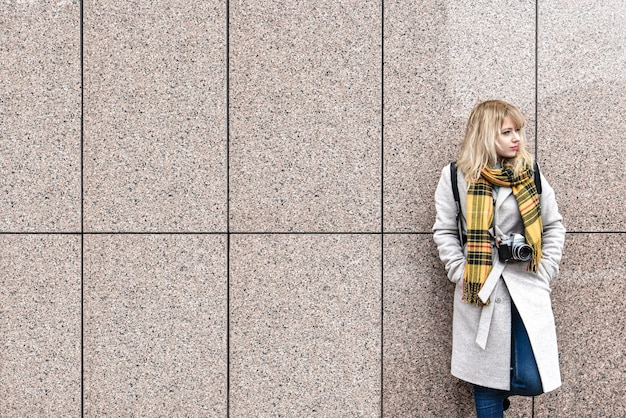 A blonde woman with a retro camera stands against the wall and looks away. free space. copy space